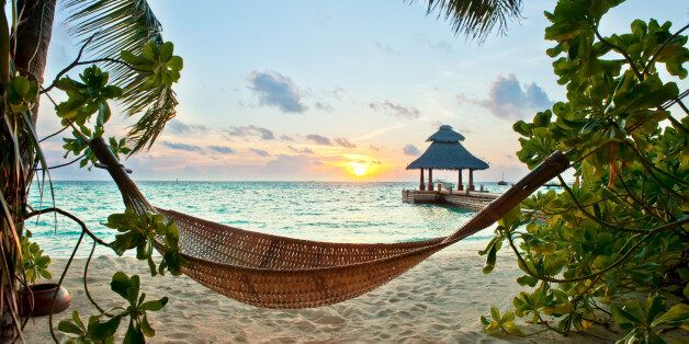 Empty hammock in the tropical beach in the Maldives at sunset