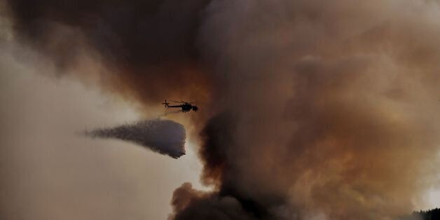 A firefighting helicopter drops waters over a fire, east of the Greek capital Athens on August 15, 2017....