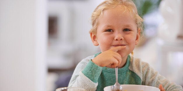Portrait of a cute little girl eating breakfast at