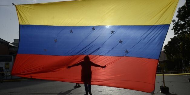 TOPSHOT - A person's shadow is cast on a Venezuelan national flag in Caracas on July 10, 2017.Venezuela...