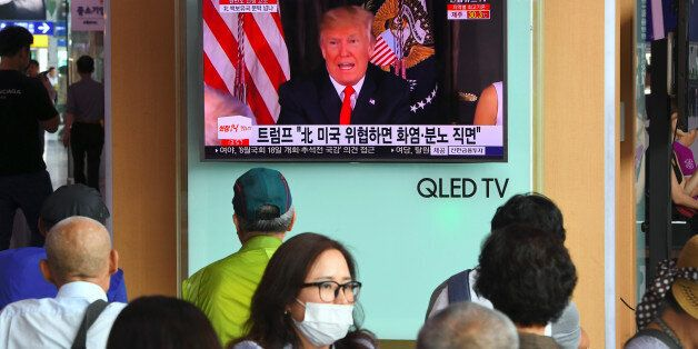 People watch a television news programme showing US President Donald Trump at a railway station in Seoul...