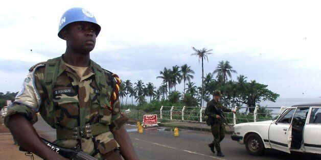 Nigerian United Nations peacekeeper guards a joint check-point with a Royal Marine Commando in Freetown...