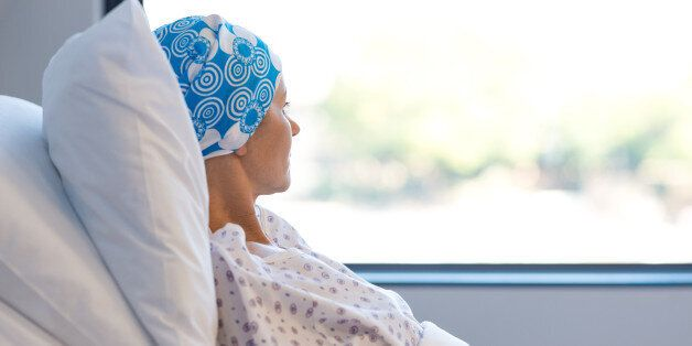 Young woman in bed suffering from cancer. Thoughtful woman battling with tumor looking out of window....