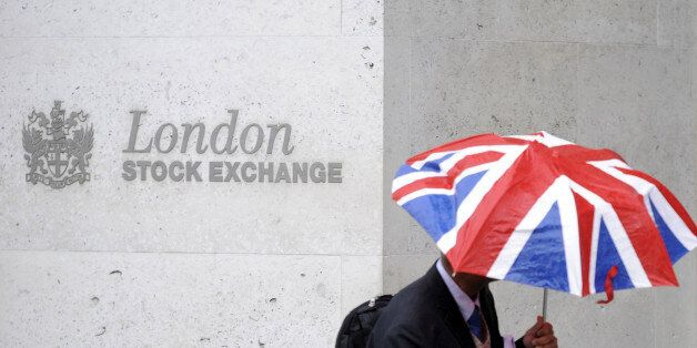 A worker shelters from the rain under a Union Flag umbrella as he passes the London Stock Exchange in...