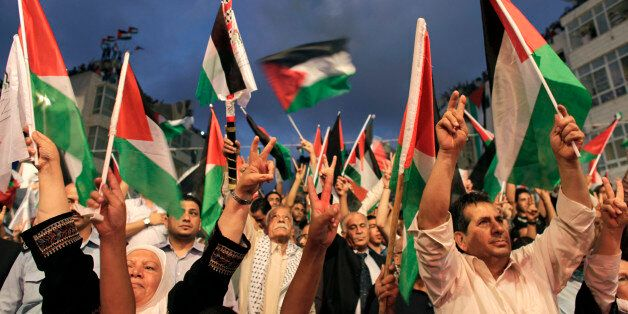 Palestinians gesture and wave flags before a public screening of Palestinian President Mahmoud Abbas'...