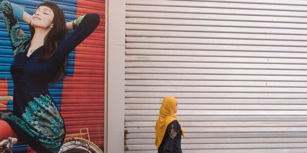 A traditionally-dressed Muslim woman walks past a poster for stylish arabic clothing in the city of Luxor,...