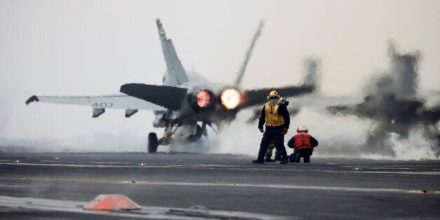 A U.S. Navy F18 fighter jet takes off from the deck of U.S. aircraft carrier USS Carl Vinson during an...