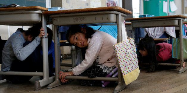 School children take shelter under desks during an earthquake simulation exercise in an annual evacuation...