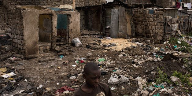 NAIROBI, KENYA - AUGUST 14: A boy walks through homes that were burned in unrest two days prior in the...
