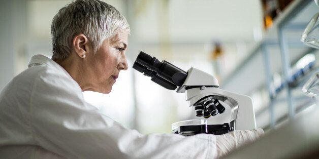 Low angle view of a mature scientist looking through a microscope in a