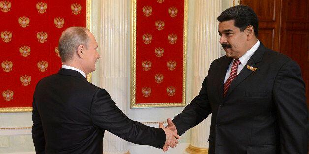 Russian President Vladimir Putin (L) shakes hands with Venezuela's President Nicolas Maduro during Putin's...
