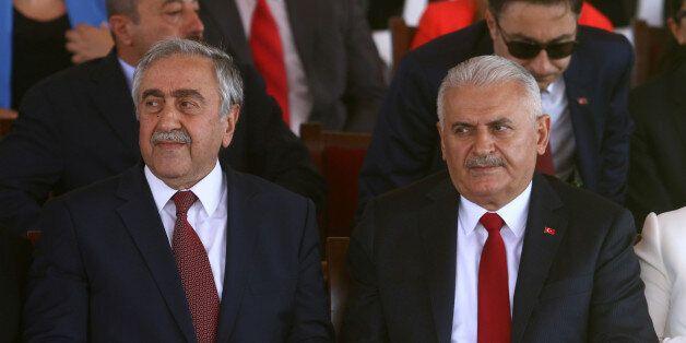 Turkish Cypriot leader Mustafa Akinci (L) and Turkish Prime Minister Binali Yildirim are seen during...