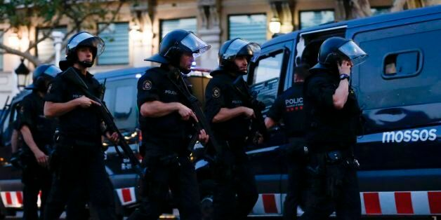 Spanish policemen walk in a cordoned off area after a van ploughed into the crowd, killing 13 persons...