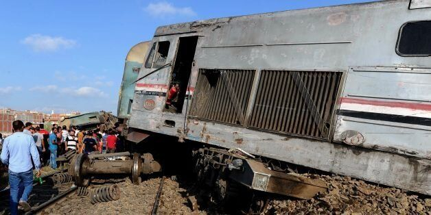 People gather at the site of a train collision in the area of Khorshid, in Egypts Mediterranean city...