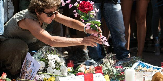 BARCELONA, SPAIN - AUGUST 18: A woman lays a flower on Las Ramblas near the scene yesterday's terrorist...