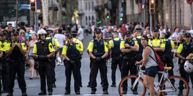 BARCELONA, SPAIN - AUGUST 18: A cyclist pushes her bike past a line of police officers on Las Ramblas...