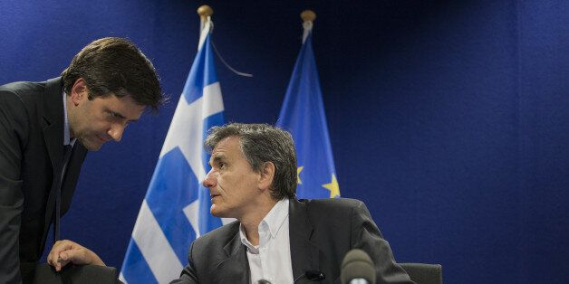 Euclid Tsakalotos, Greece's finance minister, right, speaks with a member of his team before the start...