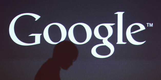 The shadow of a journalist is cast on a screen with the Google Inc. logo at a news conference in Seoul,...