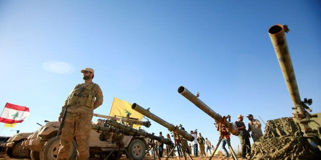 A Hezbollah fighter stands in front of anti-tank artillery at Juroud Arsal, the Syria-Lebanon border,...