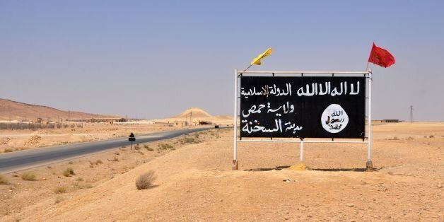 A general view taken on August 13, 2017 shows an Islamic State (IS) group poster in the central Syrian...