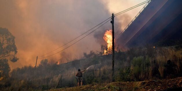 A man waters the area around his house following a new rash of forest fires ahead of a weekend of warm...