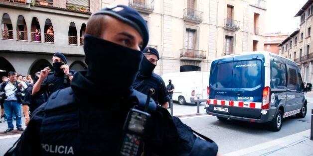 Catalan autonomous police officers, known as Mosso d'Esquadra, block a road after detaining a suspect...