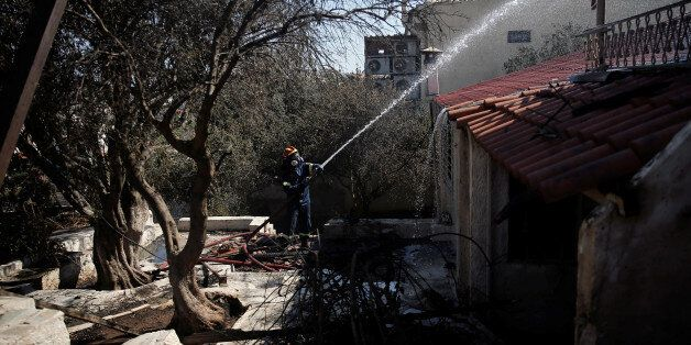 A firefighter drops water on a burnt-out house following a wildfire in the area of Kalyvia, near Athens,...