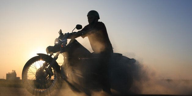 Silhouette of motorcycle and rider against blue prairie sky. Sunlight casts gorgeous shadows through...