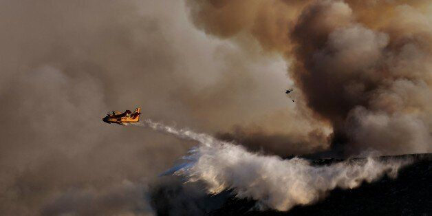 TOPSHOT - A Canadair firefighting airplane drops water above a fire at sunset, east of Athens on August...