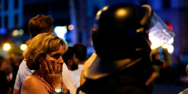 A woman gestures as she is escorted out by Spanish policemen outside a cordoned off area after a van...
