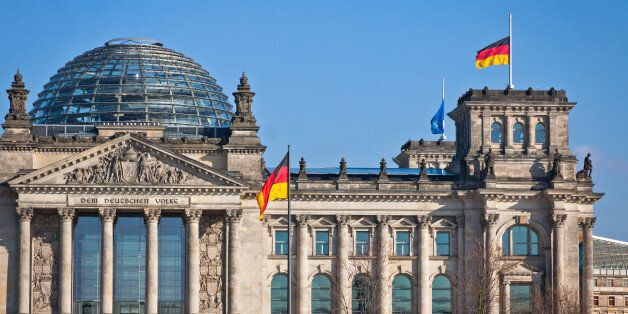 Flags of Federal Republic of Germany waving in front of the German parliament building (Reichstag) in...