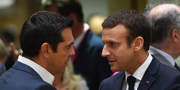 French President Emmanuel Macron (R) speaks with Greek Prime Minister Alexis Tsipras as he attends his...