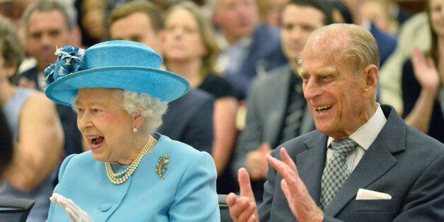 Britain's Queen Elizabeth (L) and and Prince Philip react as they listen to a school musical performance...