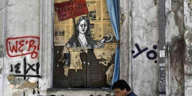 TOPSHOT - A man walks past a political graffiti in central Athens by artist Bleeps reading' Bid! a few...
