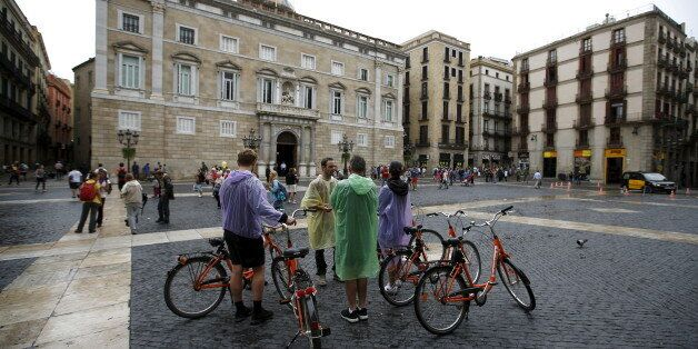 A guide speaks to his group during a bike tour at Sant Jaume square at Gothic quarter in Barcelona, Spain,...
