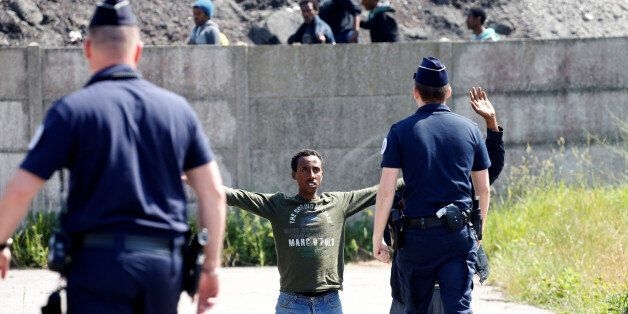 French riot police walk towards a migrant who is on his knees as French authorities block their access...