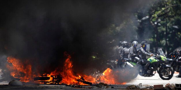 Security forces members ride near burning motorcycles as clashes break out while the Constituent Assembly...