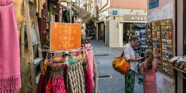 Chania, Crete, Greece - July 4, 2016: Tourists visit gift shops in Chania town on Crete
