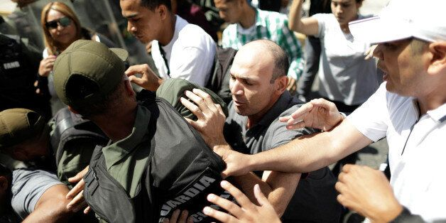 A man struggles with the national guard during a flash visit by Venezuela's chief prosecutor Luisa Ortega...