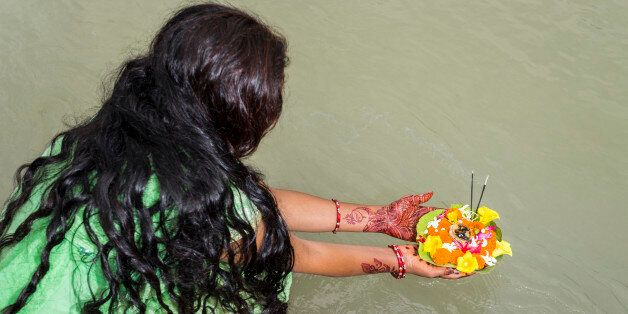 RISHIKESH, UTTARAKHAND, INDIA - 2015/06/14: A young woman with long black hair, henna painted hands and...
