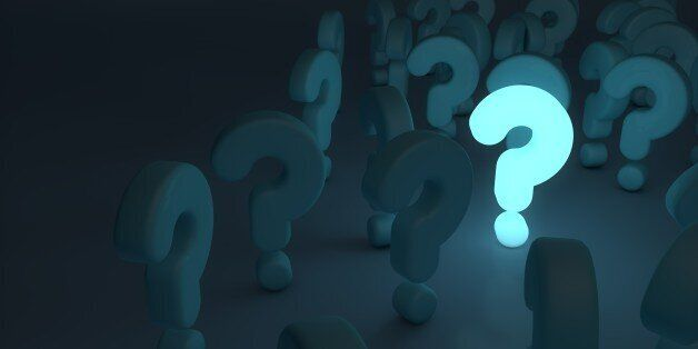 bright blue glowing question mark stands out in the dark amongst other question mark