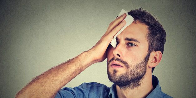 Tired man stressed sweating having fever headache isolated on gray wall background. Worried guy wipes sweat on his face