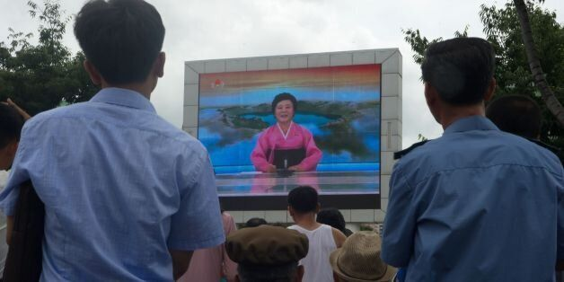 People watch as coverage relating to an ICBM missile test is displayed on a screen in a public square...