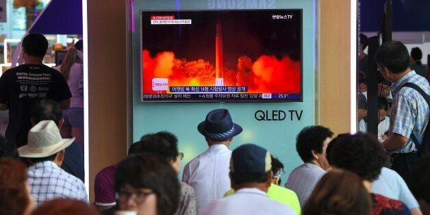 People watch a television screen showing a video footage of North Korea's latest test launch of an intercontinental...