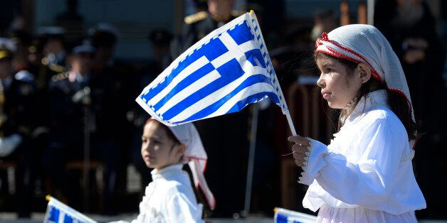 Young girls holding Greek National flags march during the parade, on the streets of Mytilene, on the...