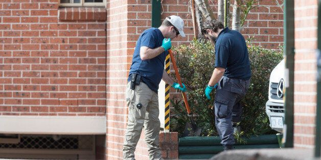 SYDNEY, NEW SOUTH WALES - JULY 30: Police officers search a garden bed of an apartment complex in Sproule...