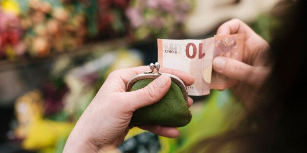 Close-up of woman paying for Flowers with a 10 Euro Bill at an outdoor