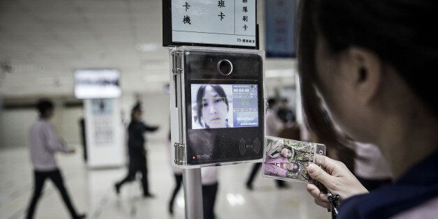 An employee uses a facial recognition device as she swipes her badge to enter the assembly line area...