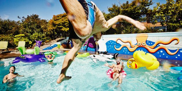 Man in mid air jumping into outdoor pool during party with friends swimming and cheering in