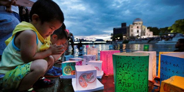 Children pray after releasing paper lanterns on the Motoyasu river facing the Atomic Bomb Dome in remembrance...
